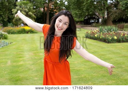 young woman with outstreched arms in the park
