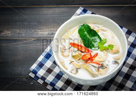 coconut milk soup with chicken or Thai chicken coconut Soup ( Tom Kha Gai ) on wooden with table cloth table top view Thai local food