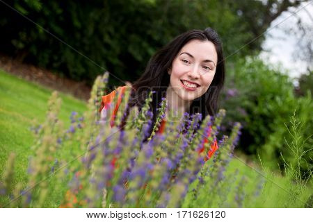 young woman next to purple flowers in the park