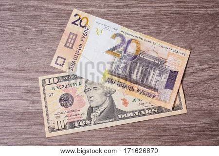 New belarusian money and ten dollars. The course of the Belarusian money currency devaluation. Money lying on the wooden background