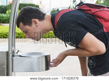 Man Drink Water From Drinking Fountain At Street