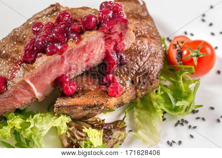 Beef steak with spices and seasonings and sliced pieces of tomato cherry and berries. A big piece of meat. Steak. Grill beef steak. Traditional Italian appetizer parma ham with melon - prosciutto melone.