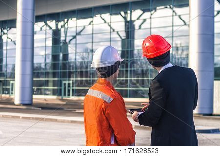 young boss and worker in conversation discussing a construction project on tablet. They wear safety helmets. Business modern background