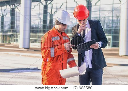young boss and worker in conversation discussing a construction project. They wear safety helmets. Business modern background