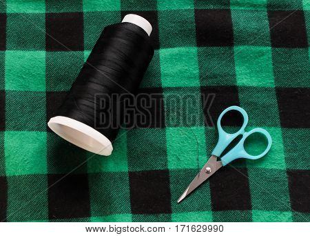 Black threat with scissors on green fabric