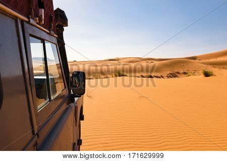 Side of an four by four oldtimer off-road vehicle driving in the sand dunes of the Sahara desert in Morocco.