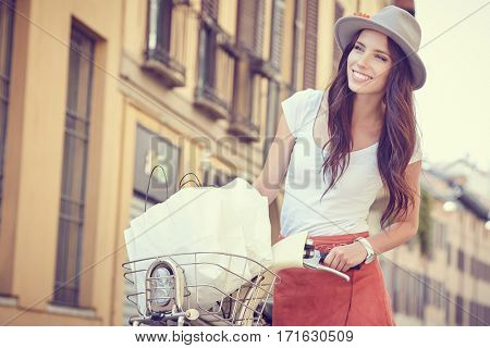 Young woman walking with her bicycle in the city