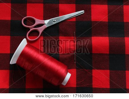 Red threat with needle and scissors on colorful fabric. View above