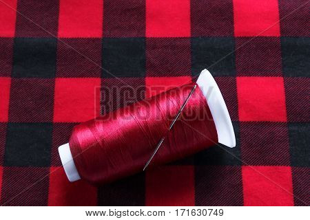 Red threat with needle on fabric .