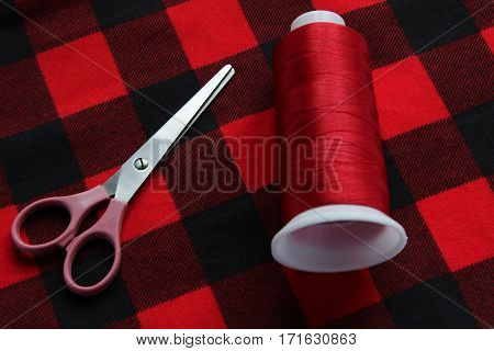 scissors and threat on a red fabric