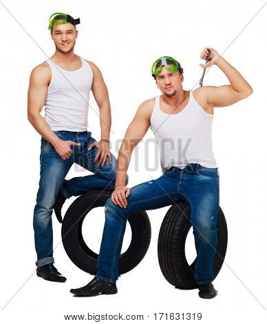 dancers dressed as car mechanics with tools and tire, isolated against white background