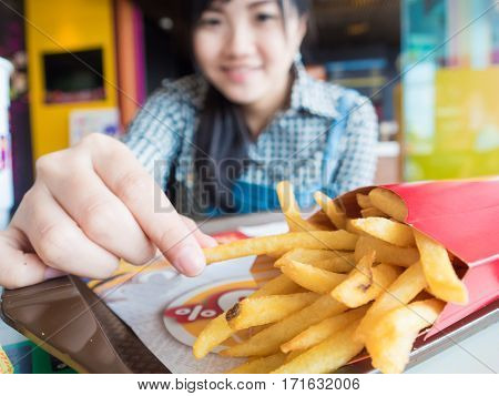 Beautiful Young Asian Girl Eating French Fries