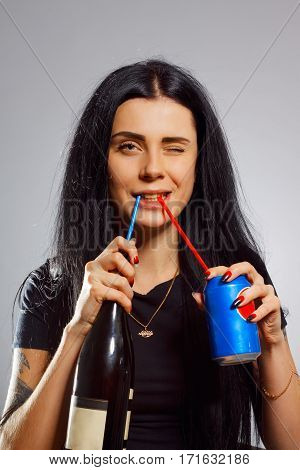 Funny pretty girl drinking wine and cola over grey background