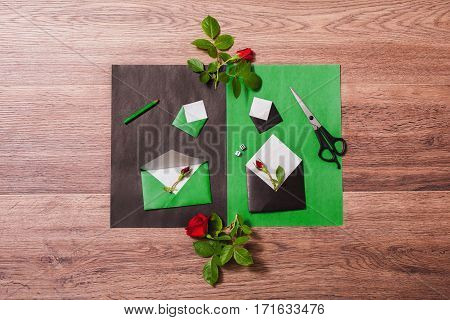 Color paper. Small colored envelopes. Workplace designer. Romantic letter. Flower arrangement with stationery items. Red roses with green leaves on wooden background. Flat lay. Dice for good luck