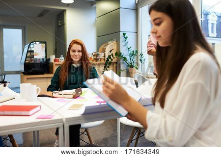 Young female student to practice in a successful business company keeps records of advice from professionals. Attractive student girl preparing for exam with her classmates in university library