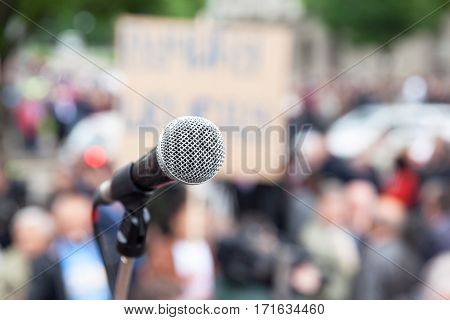 Microphone in focus, blurred crowd in background. Political rally. Protest. Public demonstration.