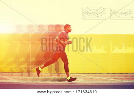 Full length portrait of male runner with muscular body in tracksuit jogging against yellow wall with copy space area for text message or content Motion blur effect with progress infographics diagrams