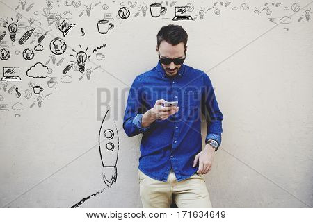 Bearded modern businessman browsing internet via mobile phone hipster guy personalizing multimedia programs and applications on contemporary cell telephone while standing against copy space wall