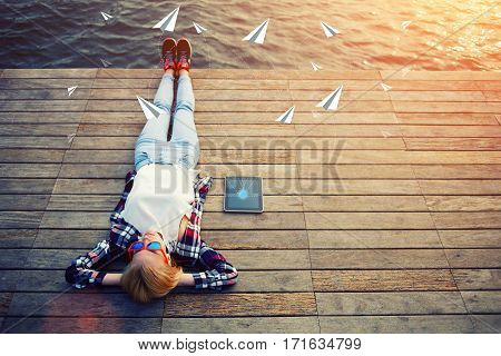 Top view young woman lying on a wooden jetty and enjoying the sunshine while files are loaded to the cloud by networking connection on touch pad. Infographics design elements of outgoing messages
