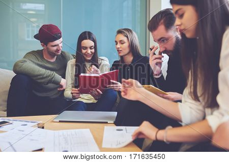Group of young journalist sharing opinions and ideas about latest news reading press release talking about improvement of article editing mistakes in friendly atmosphere sitting in coworking office