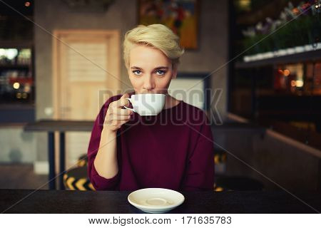 Young female hipster girl has a cup of coffee in morning before starting work day. Beautiful woman drinking tea in modern cafe she is dressed in hoodie with copy space area for advertising brand name
