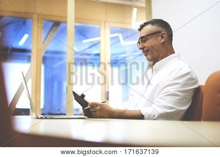 Skilled man programmer develops application software meanwhile it uses laptop computer and a notebook to record-keeping. Handsome mature businessman in eye glasses write notes after read e-mail letter