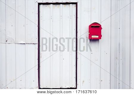 The bulk industrial white wall with a door and a red mailbox conceptual image suitable for different types of advertising. Background for your promotional content or website paper