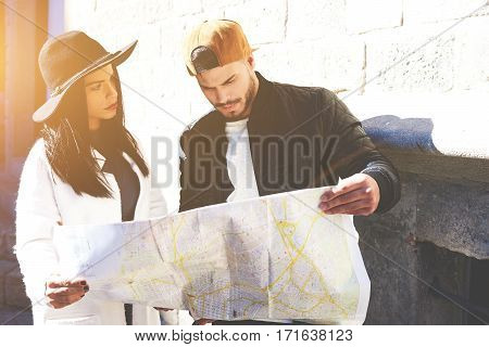 Young couple of the tourists got lost in the old center looking for the way to the hotel with a city map. Hipster girl and her boyfriend using tour guide during walk in historic center of Barcelona