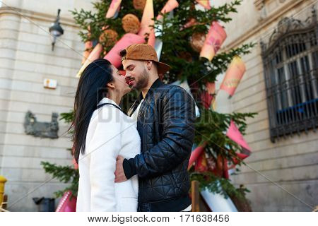 Young couple walking in the city at the weekend enjoying the nice weather and each other. Stylish man looks into the eyes of his beloved with tenderness and warmth. Girlfriend smile to her beloved.