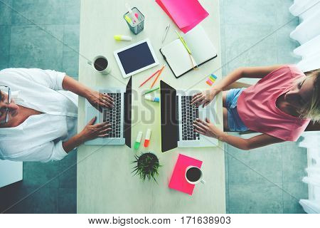 Top view of office workers desktop. Young student and a middle-aged woman keyboarding on laptops.Touch pad notebook and two cups of coffee. Different age categories for the use of modern technologies