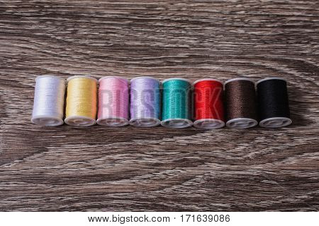 Colored thread lie on a wooden background. flat lay top view.
