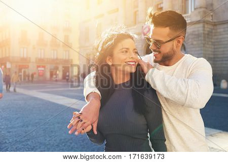 Happy young couple is spending vacation holidays in Barcelona city. Both look really happy. They are strolling along the streets of the old town and hanging out with pleasure seeing attractions.