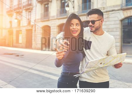 Cheerful people who get lost in Barcelona found the right way.Hipster ma with glasses holding a map and elegant brunette smiling and shows him the direction.They are ready to continue their journey