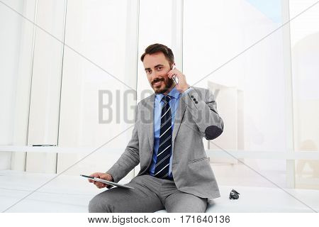 Male owner enterprise with pouch pad in hand is calling via smart phone while is sitting in his private office interior. Confident man manager is smiling for camera during cell telephone conversation
