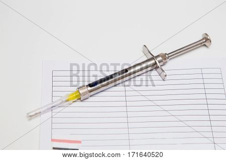 Surgical steel dental syringe with anesthetic cartridge on a white dentist table