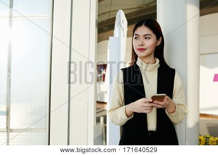 Young Asian woman successful economist is waiting for a call from her college while is standing in hallway office building near copy space for your advertising text message or promotional content