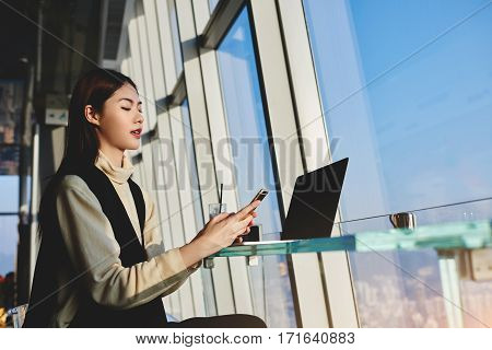 Young Asian woman skilled office worker is reading e-mail on her mobile phone while is waiting reboot her laptop computer with blank copy space screen for your advertising text message or content