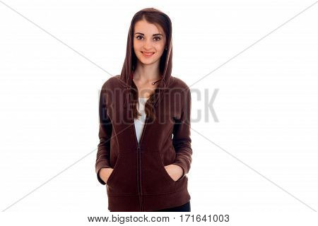 Cutie young brunette student in brown sport clothes with hood posing and smiling isolated on white