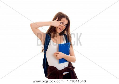 Cutie young brunette student with blue backpack on her shoulders posing isolated on white