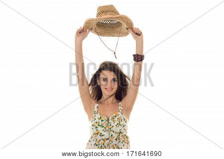 cheerful young girl in sarafan with floral patter and straw hat with wide brim smiling and looking at the camera isolated on white