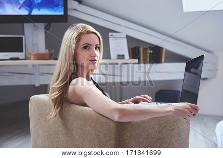 Beautiful Caucasian woman student is looking at the camera while is sitting with laptop computer in modern loft interior. Pretty young hipster girl is using portable net-book to find the desired file