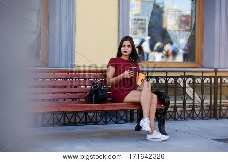 Gorgeous woman with mobile phone in hands is thinking about text message from her boyfriend what she just received. Young lovely female is holding cell telephone while is sitting outdoors on a bench