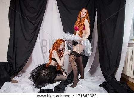Two red sexual girl with blue eyes and pale skin on a black and white background. Women lesbian girl. Long red hair. Fetish model. Look at the camera. Beautiful underwear.