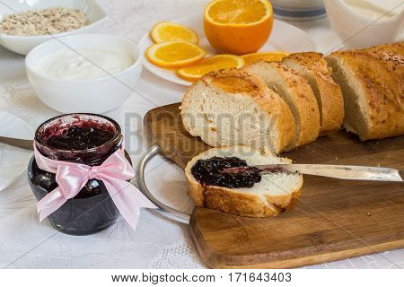 Jar of currant jam on table with loaf of bread cream and oatmeal orange. Healthy breakfast