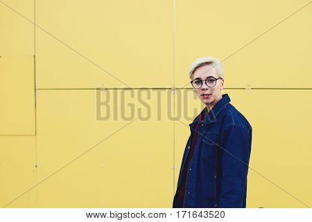 Young attractive blonde female hipster dressed in trendy jeans jacket and sweatshirt spending free time outdoors while having city tour alone standing on copy space area for your advertising content