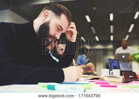 Portrait of bearded male writer on frontage thinking over his new poetic book writing down ideas into notebook with pen during informal meeting sitting in coworking office concentrated on his job