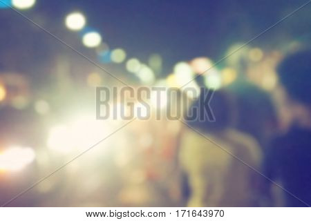 People walking on footpath has car lamp lighting blur at Pattaya the city Near street road in the night times are bokeh circle shape lighting Thailand trip retro color tone.