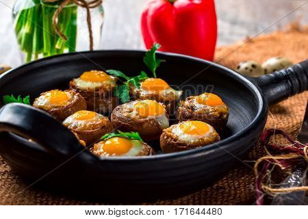 Mushrooms with quail eggs. Mushrooms on black pan. Quail eggs pepper paprika parsley and cutlery close. Selective focus