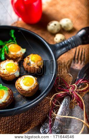 Mushrooms with quail eggs. Mushrooms on black pan. Quail eggs pepper paprika and cutlery close. Selective focus