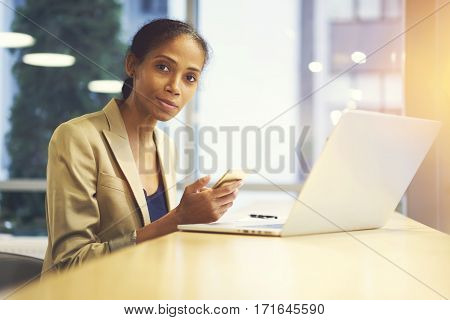 Portrait of official dressed female leader of businnes company preparing for formal meeting with colleagues searching information in internet via smartphone and laptop using wifi in coworking office
